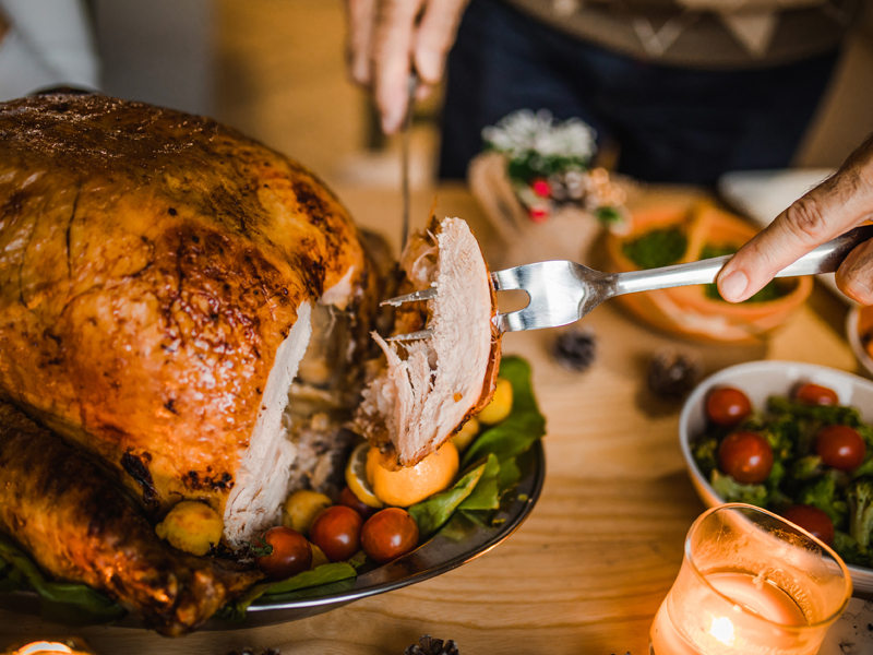 Thanksgiving turkey being cut on table; learn how to safely thaw a frozen turkey.