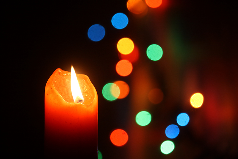 Candle with Christmas decorations; learn about holiday mental health.