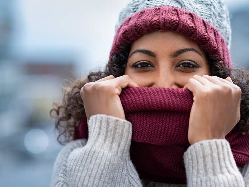 Woman with scarf over face; follow these healthy winter tips.
