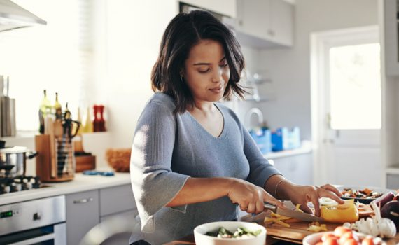 Woman cooking in kitchen; measure weight loss success without the scale.