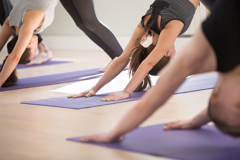 Several women doing yoga, which is a recommended activity for people living with scoliosis.