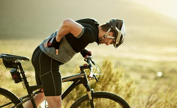 Man on bike holding back; a neurosurgeon talks about back pain and bike rides.