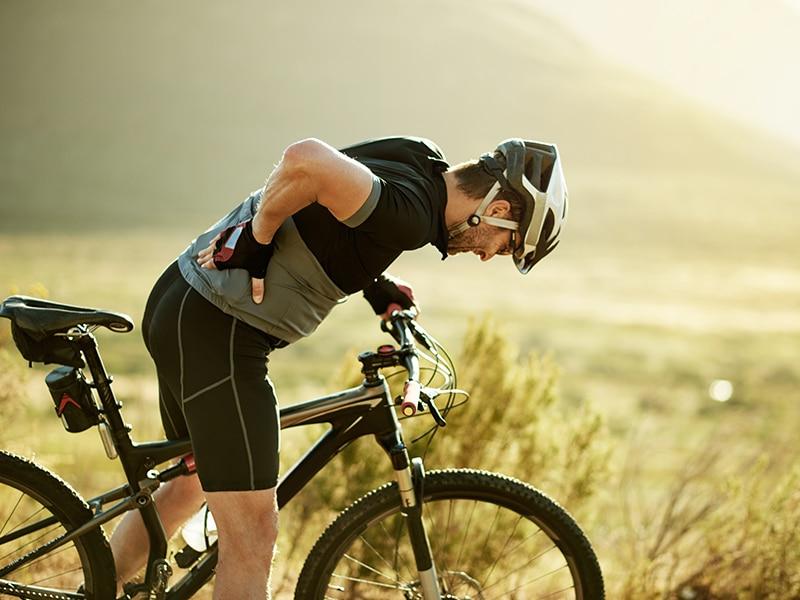 Man on bike holding back; a neurosurgeon talks about back pain and bike rides.