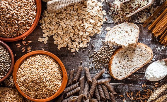 Good and bad carbs lying on table like brown rice, bread and oatmeal.