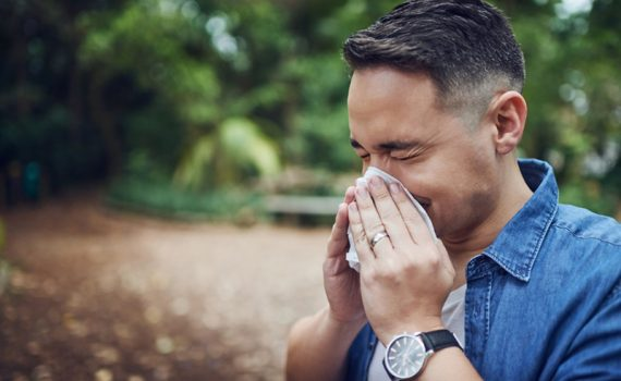 Man blowing his nose outside; allergies are bad in North Texas.