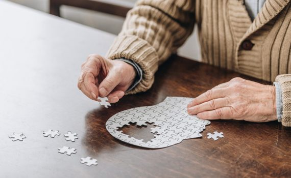 Person doing a puzzle of a head where puzzle pieces are missing in brain; Alzheimer's support can help those who deal with it.