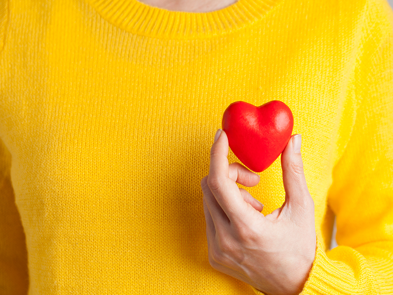 Woman holding a red heart next to a yellow sweater; women and heart attack symptoms.