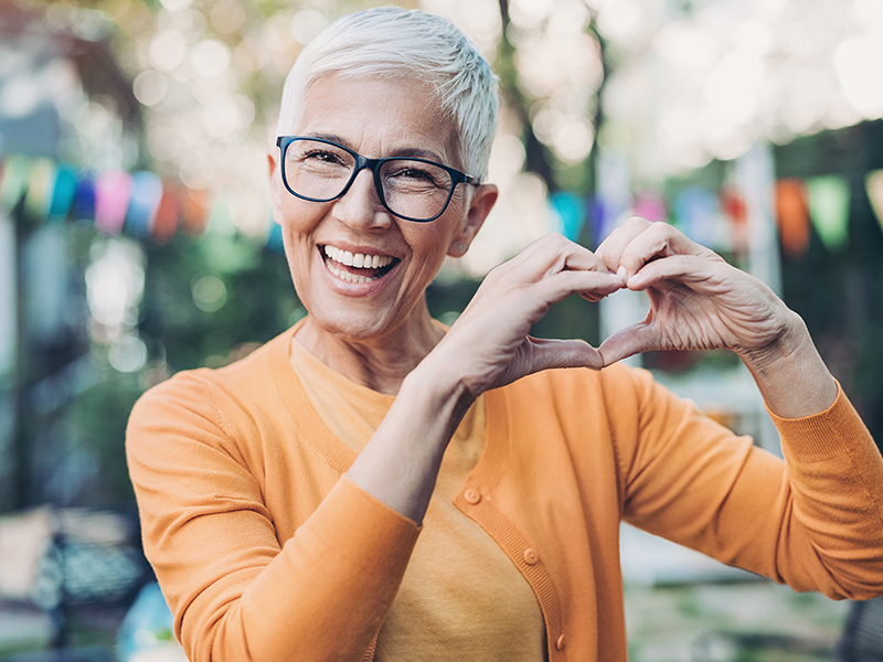 woman with her hands in the shape of heart in front of her chest; heart health mistakes to avoid