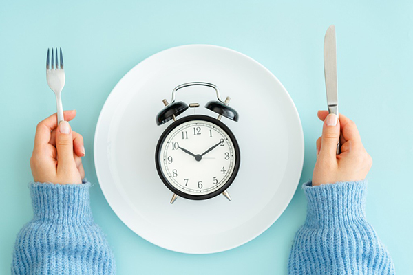 Clock on dinner plate; learn if intermittent fasting is right for you