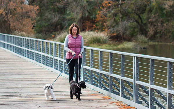 Woman bonds with her two dogs by exercising.