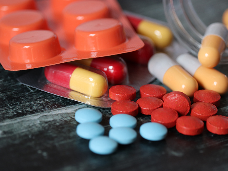 Medication and prescription pills gathered on table, used to explain COVID-19 remedies