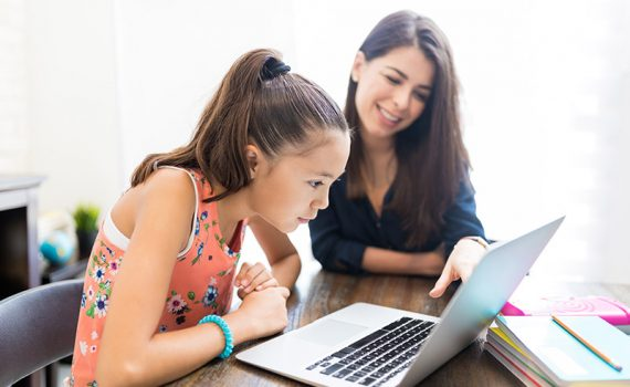 A young girl uses a laptop for home-schooling as her mom sits beside her.