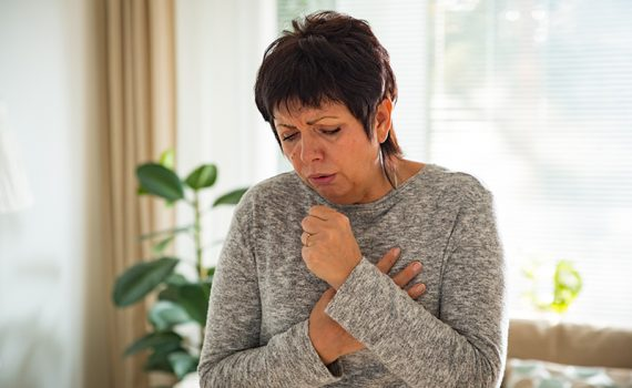 Woman coughs, showing possible symptoms of COVID-19, flu or cold.