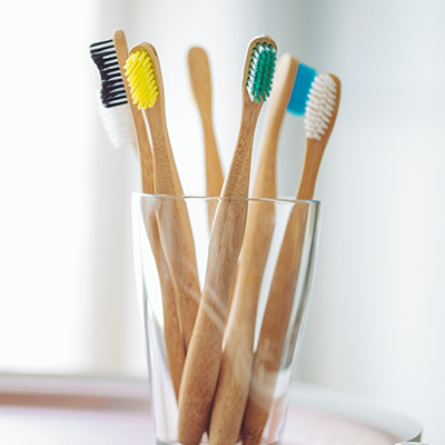six toothbrushes resting in glass cup on countertop