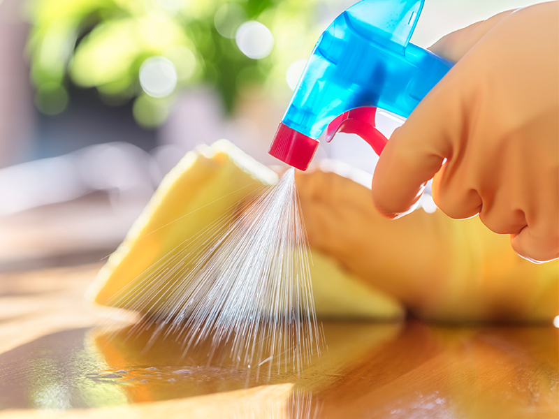 Person spraying cleaner and wiping with rag, cleaning surfaces in the home that may have germs