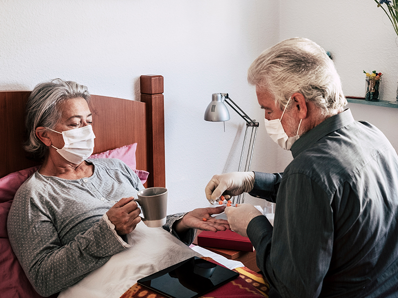 Man administering care for ill woman in bed at home, both wearing masks protecting from COVID-19