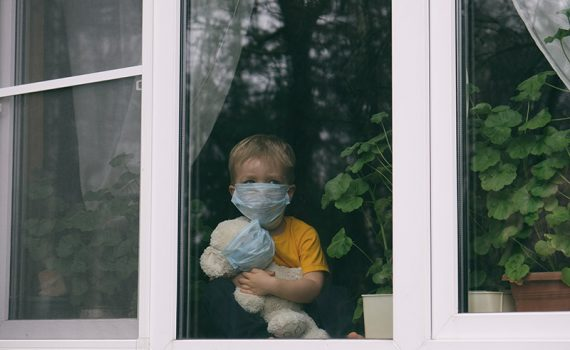 child looking out of window wearing face mask to protect against COVID-19