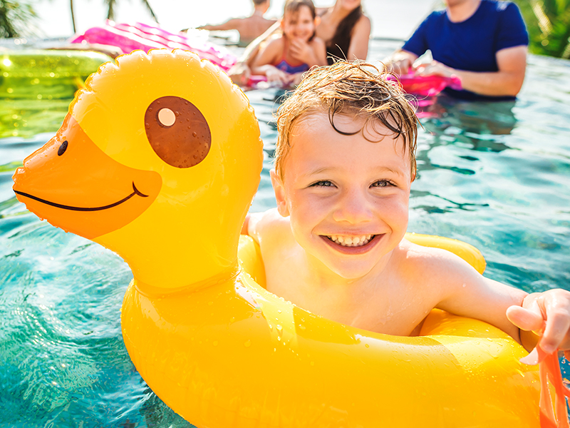 red haired boy smiling at camera while floating in pool in duck inflatable float.