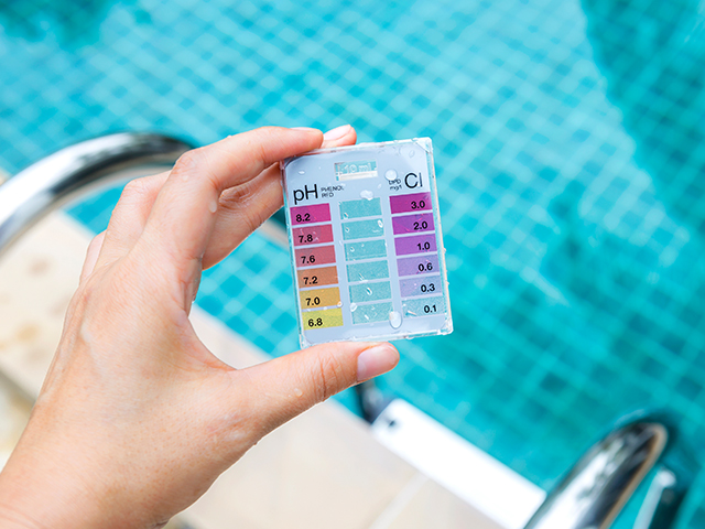 person holding pool water testing kit to check for pH level of the water