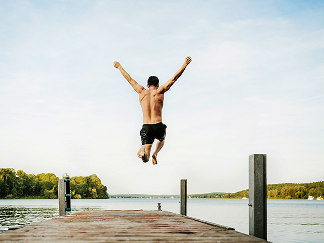 man wearing black swim trunks with arms extended up in the air jumping off wooden dock into a lake on an overcast day