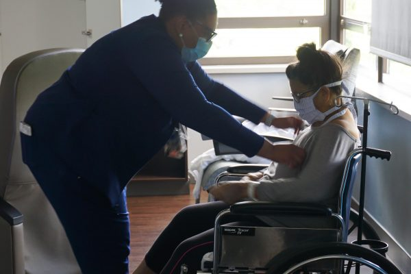 barbara winn in wheelchair receiving care from nurse in scrubs