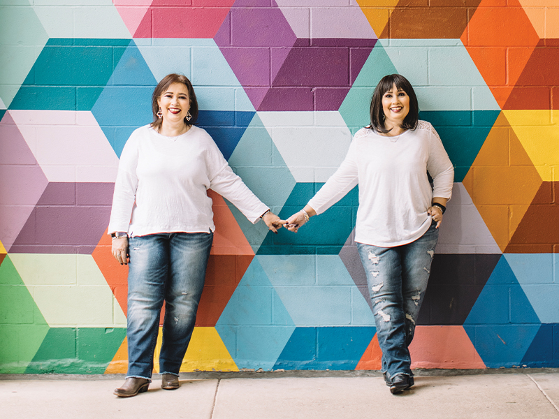 Twin sisters Yvette and Yvonne, standing in front of colorful rainbow wall mural after Yvette's victory over breast cancer with the help of Methodist Charlton Medical Center