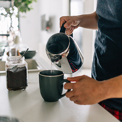 photo of a man pouring coffee into a mug