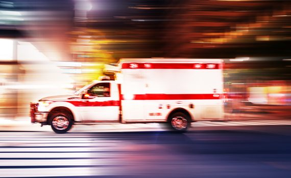ambulance driving quickly through a street at night, used to explain COVID-19 fears