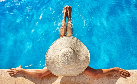 Woman sitting in a pool wearing a summer hat