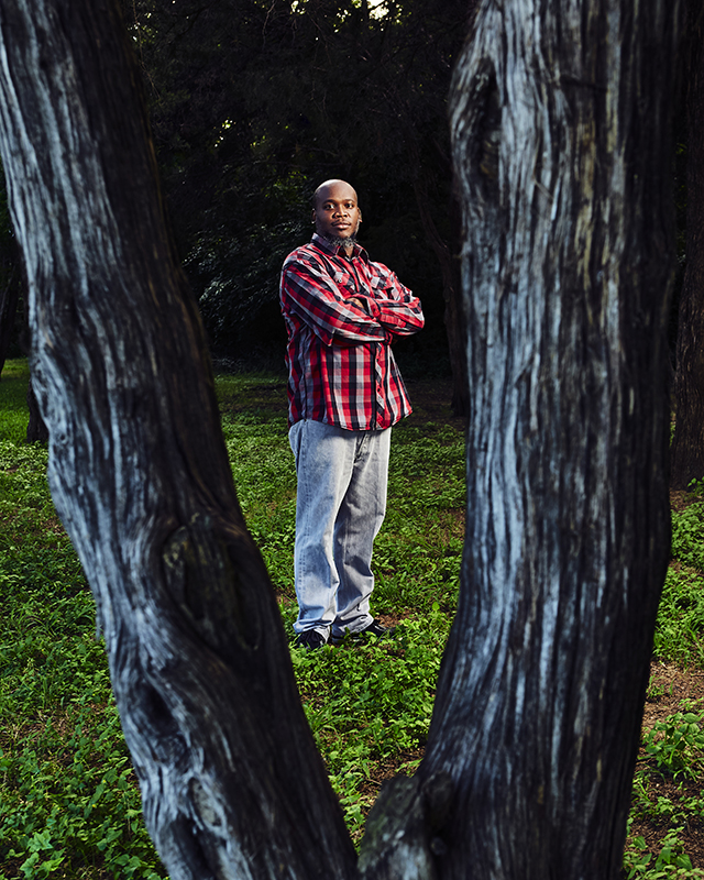 Methodist Dallas patient Marcus Hawkins standing between trees and looking to camera, after experimental drug allows him to fight off COVID-19