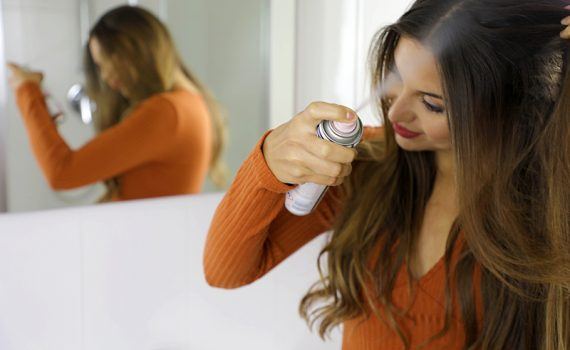 Stock image of woman using dry shampoo on her hair, used to explain the relationship between dry shampoo and hair loss