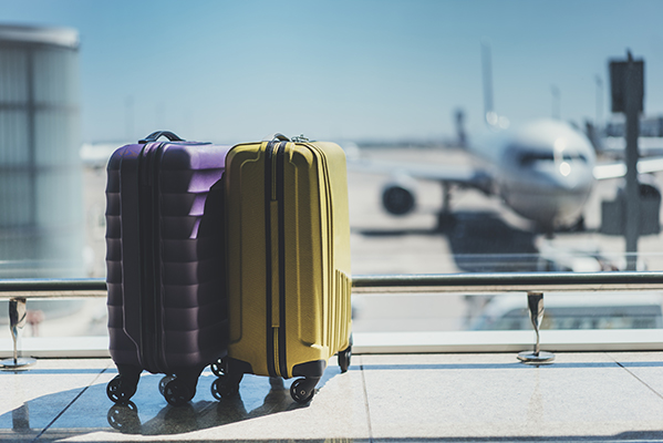Purple and yellow suitcases in airport terminal