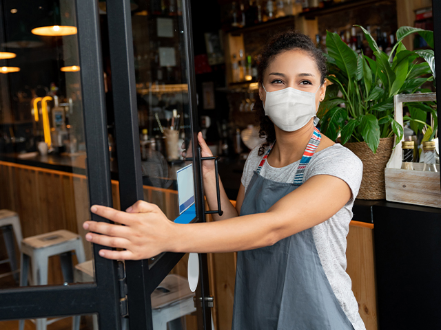 Woman wearing mask and apron opening up doors to bar/restaurant, used to explain COVID-19 and its relationship with heat