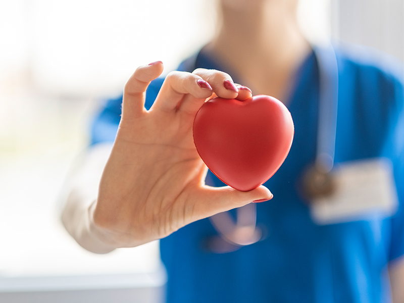 Hospital staff member holding heart object, used to explain stress and COVID-19