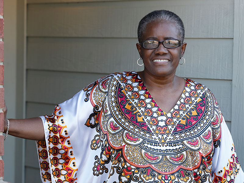 Letitia Lewis-Robinson smiling at camera in colorful blouse after her recovery from COVID-19