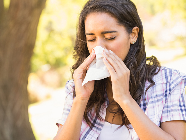 Brown haired woman blowing nose into a tissue while outside
