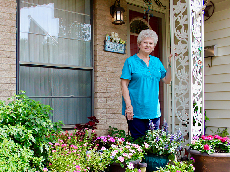 Barbara Niland standing in front of her home after Mako robotic surgery to replace her knee