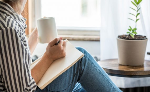 Women in striped blouse and blue jeans with notebook propped against her thighs and sipping from a mug, reflective of self-care during the pandemic