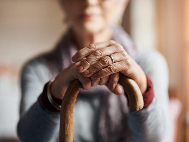 Person looking at the camera, focused on their hands and cane in the foreground.