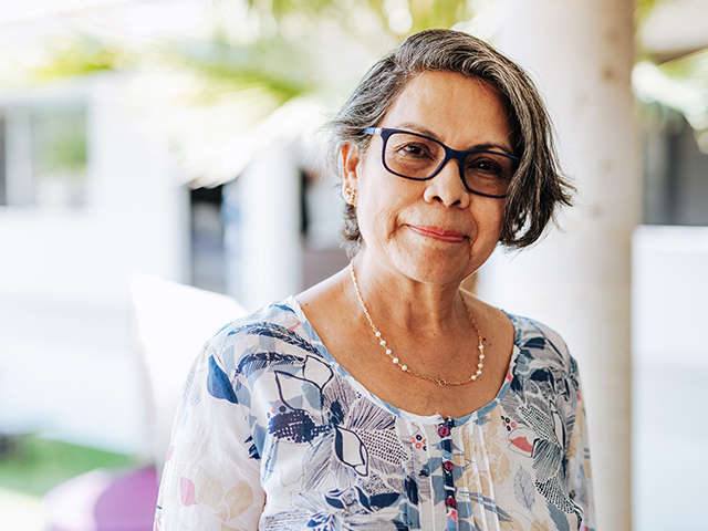 Middle aged woman with glasses and floral blouse looking at camera