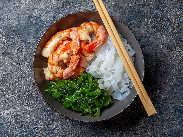 Bowl with chopsticks, noodles, greens, and shrimp