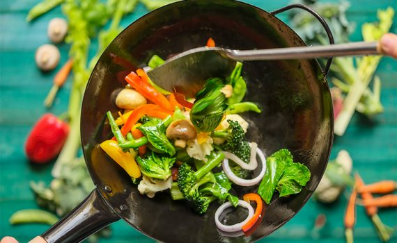 A variety of fresh market vegetables including broccoli, carrot, capsicum, snow peas, red onion, green beans, celery and mushrooms being stir-fried and cooked in a hot wok, with an out of focus turquoise-colored wooden, vegetable covered table in the background.