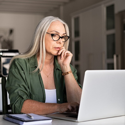 Woman with black glasses looks at laptop with her left hand on her face