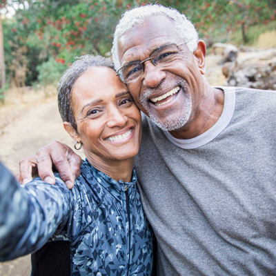 Older man and woman smile while taking selfie