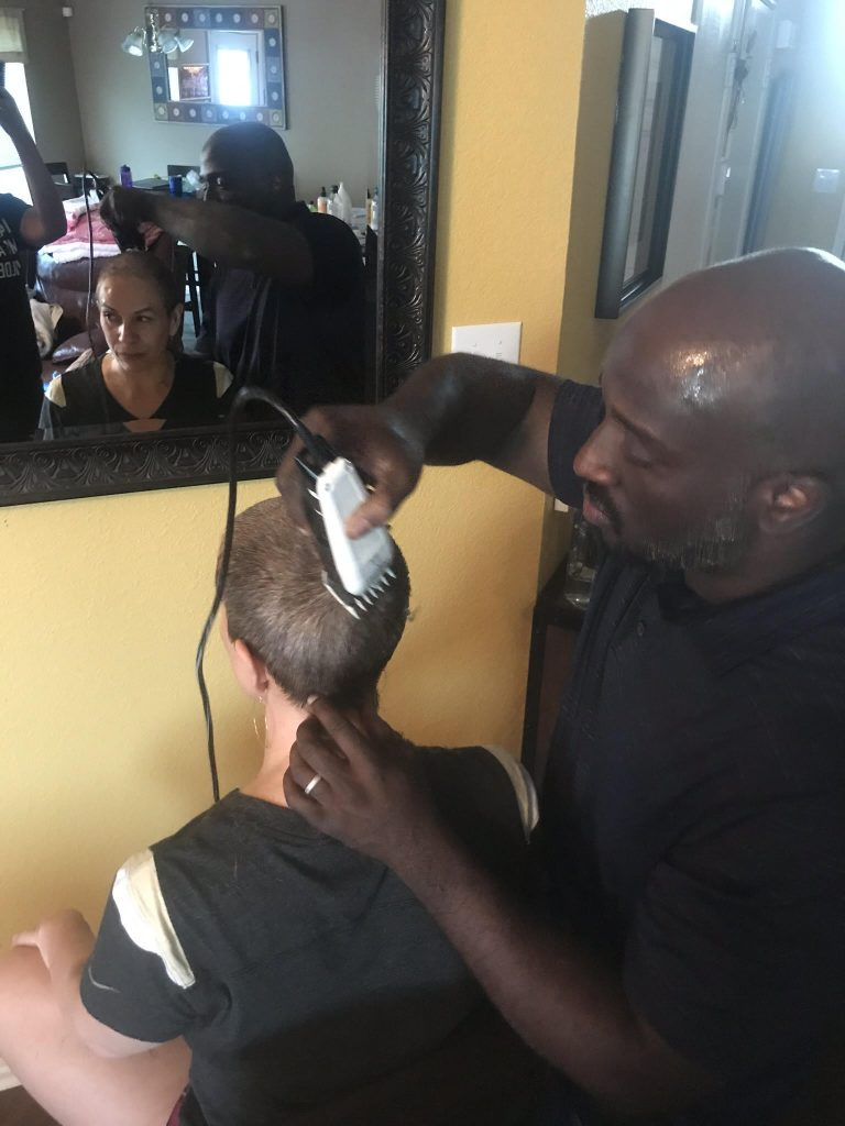 Michelle having her head shaved during breast cancer treatment
