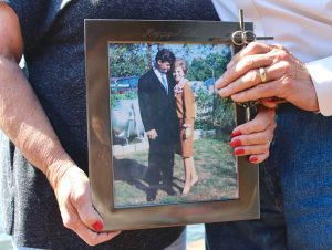Kathy and Chuck Magers holding a photo from when they were young, after Chuck's treatment of pancreatitis