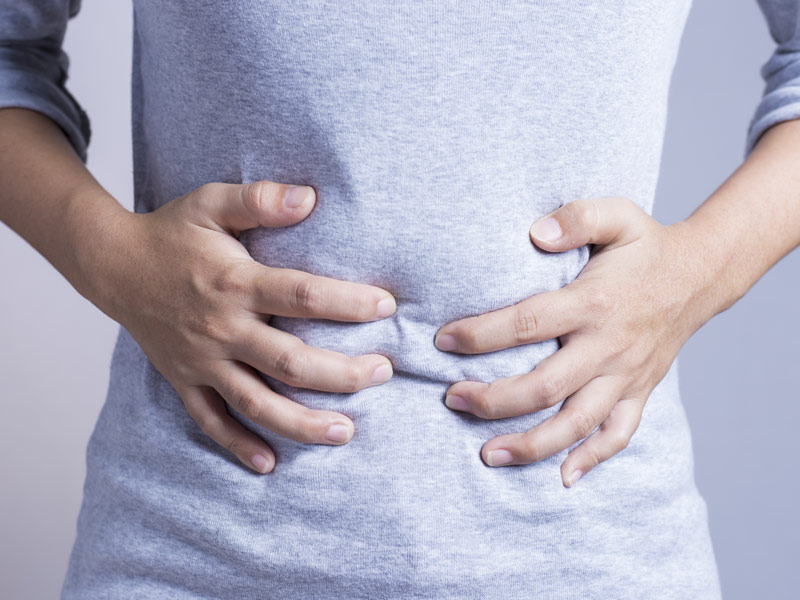 Person grabbing their stomach, image representation of a stomach ache or gastrointestinal pain