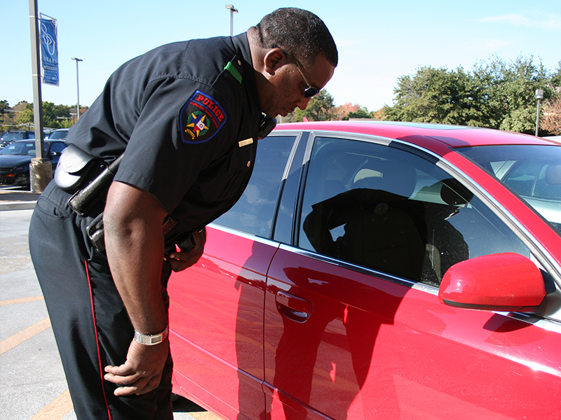 A hospital police officer looking into red car passenger seat window