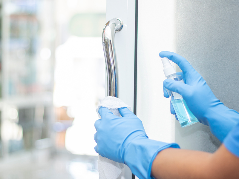 sanitizer spray cleaning a surface by a person wearing blue gloves, used to explain the coronavirus and germs in 2020