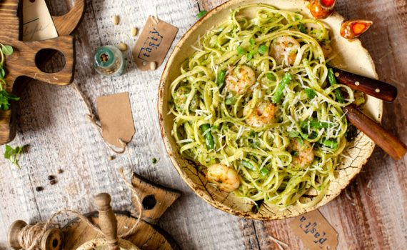 Italian food dish with shrimp and pesto with spaghetti in a wooden bowl, resting on a tablecloth and wooden table